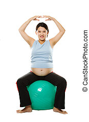 Pregnant woman - A pregnant woman exercising with an...