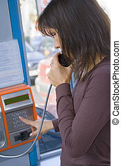 Public phone call - Girl dialing the number in a public...