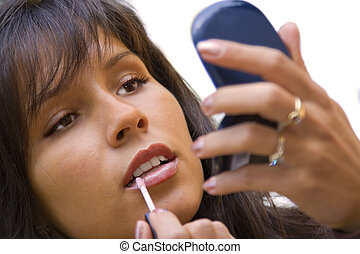 Applying lipstick - Close-up image of a young woman applying...