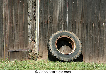 Tire leaning on a old barn - A Tire leaning on a old barn