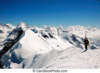 Mountaineer walking on a snowed ridge, West Alps, Swiss.