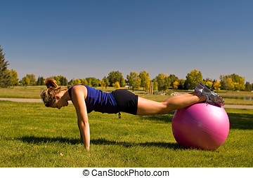 Push ups - Young woman doing push ups with an exercise ball.