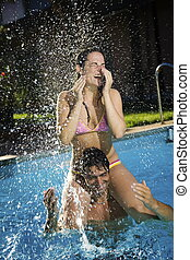 Healthy lifestyle: couple having fun at the swimming pool
