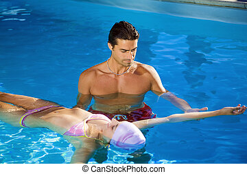 Healthy lifestyle: girl taking swimming lessons in a...