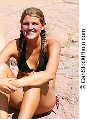 Pig Tails - A young woman sitting outdoors on natural canyon...