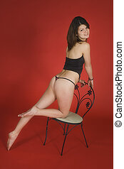 Tiffany - Young woman posing on a red background in a thong