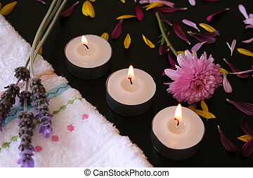 Three flames - Three teelights next to a hand towel with...