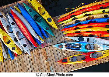Kayaks on a dock waiting for some paddlers