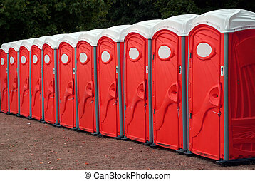 Row Of Red Portable Toile - A row of portable red toilets at...