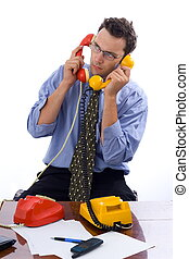 Talking on two telephones - Busy businessman talking on two...