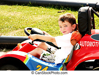 Boy in race car - a little boy is driving a racing car