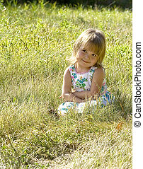 Little Girl in grass - a cute little girl is sitting in the...