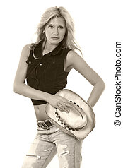 Cowgirl attire - Beautiful blond woman holding straw cowboy...