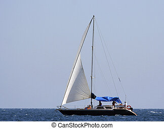Sailing yacht with having a rest people in the sea