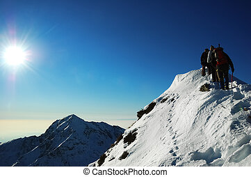 mountaineers - Group of mountaineers climbing a mountain...