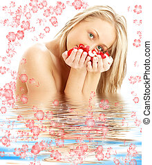 blond with red and white rose petals in water with flowers...