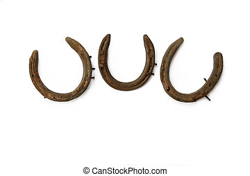 Triple Luck - Three old rusty metal horseshoes against a...