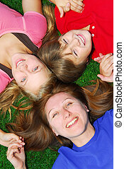 Family lying down on grass - Portrait of a family - mother...