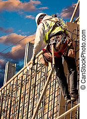 On the Wall at Dawn - A construction worker on a high wall...