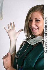Nurse putting on gloves - A nurse is putting on gloves with...