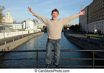 Loud shout. The young man against the river in Moscow.