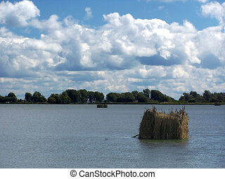 Duck Hunting Blinds - Duck Blinds in lake with dramatic sky...