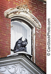 Gargoyle on on Old House - Gargoyle perched in front of a...