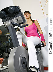 health club: young girl working out on a cyclette