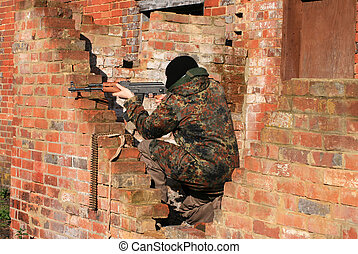 Hooded gunman with AK47 in the aiming position using brick...
