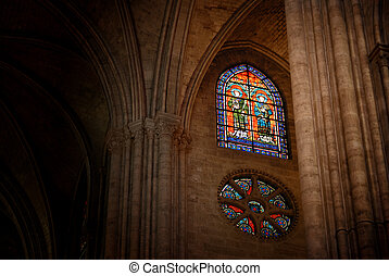 Interior shot featuring a stained glass window in Notre Dame Cathedral in Paris, France. Image has an added film grain effect.