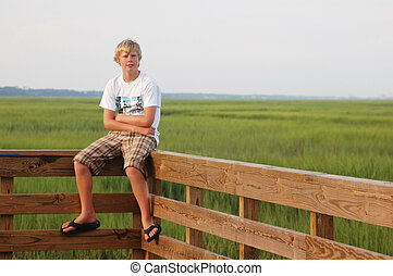Teen Sitting on Fence - Young teen sitting, looking away, on...