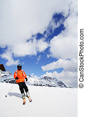 Skier in bright colored outfit skiing down a ski slope in...