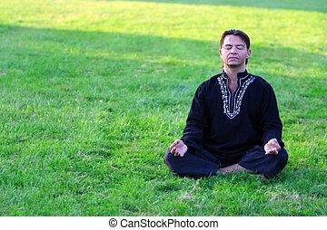 Zen master - Man sitting cross legged in a zen position with...