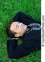 Zen master - Man lying on the grass in a zen position with...