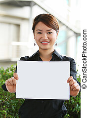 Asian girl - Asian chinese girl smiling and presenting blank...
