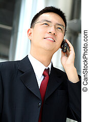 Business man - Good looking asian business man talking into...