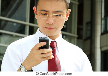 Business man - Good looking asian business man smsing on a...