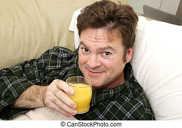 Morning OJ - A man sick at home drinking his morning orange...