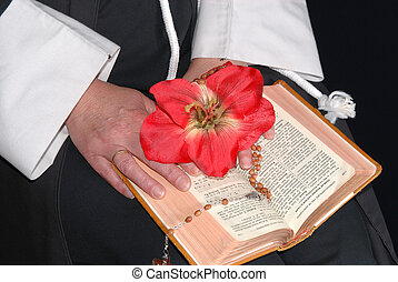 nun hands with flower on bible - Nun hands resting on the...