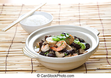 Chinese food - A shot of seafood casserole with a bowl of...