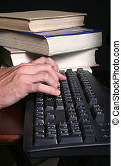 Hands on keyboard - hands on keyboard and a stack of books