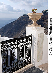 Gate and Urn - A wrought iron gate on a white fence in...