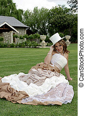 Bride Sitting - A bride sitting on grass holding a hat