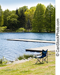 Lawn Chair - A lawn chair sitting next to a lake