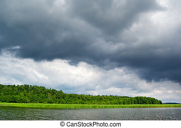 Moody sky over lake. - Stormy clouds over the lake. Mazury,...