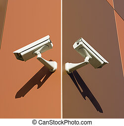 Brown Cameras - Two security cameras attached on building...