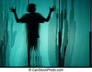 boy trapped - boy silhouetted against acrylic suggesting...