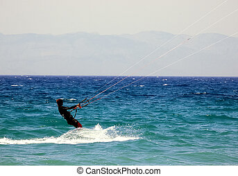 Kite surfer over blue sea