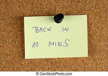 Back in 10 minutes - Yellow small sticky note on an office...