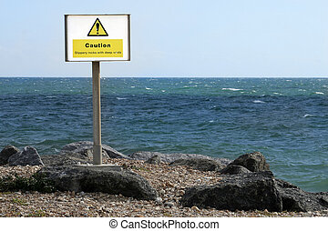 Take care at the sea - Sign urging caution by the sea -...